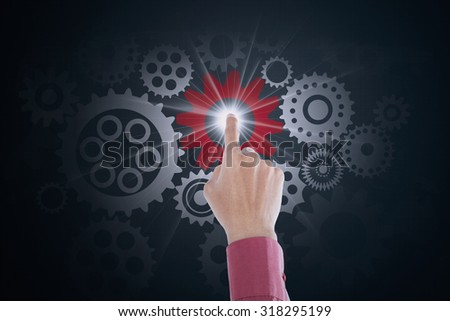 Image of entrepreneur hand touching business gear on the futuristic screen. Mechanism concept