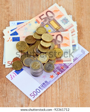Image of euro currency: coins and banknotes on the wooden surface - stock photo