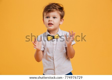 Image of excited little boy child standing isolated over yellow background. Looking aside.