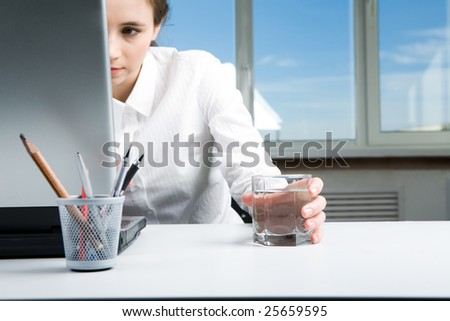 Image of executive female looking into laptop display and keeping hand on glass of water in office