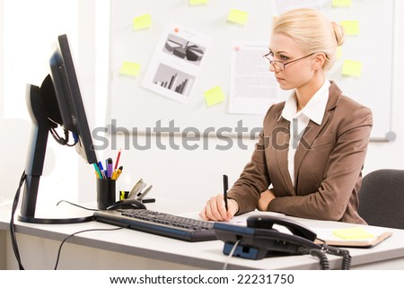 Image of executive lady sitting before computer in office and working - stock photo