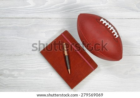 Image of executive notepad, pen and American football on white rustic wood. Playbook concept for game plan. - stock photo