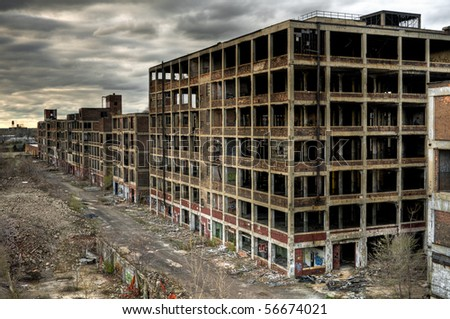 Image of exterior of abandoned warehouse with destroyed walls, broken windows and mass destruction. - stock photo