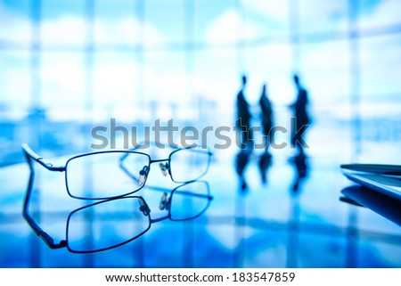 Image of eyeglasses at workplace and its reflection with businesspeople standing on the background - stock photo