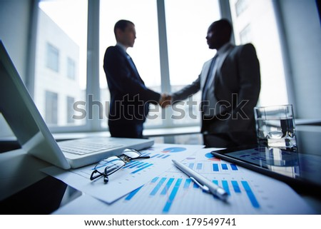 Image of eyeglasses, glass of water, pen, laptop, touchpad and financial documents at workplace with businessmen handshaking on background - stock photo