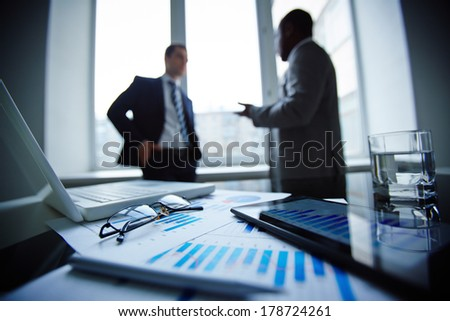 Image of eyeglasses, pen, glass of water, touchpad and financial documents at workplace with businessmen communicating on background - stock photo