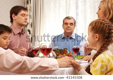 Image of family members praying at festive table while holding each other by hands