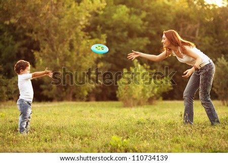Image of family, mother and son playing frisbeel in the park. - stock photo