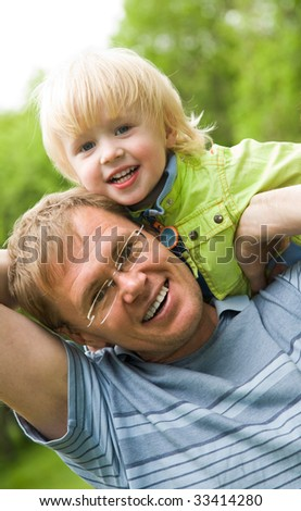 Image of father holding his son and smiling - stock photo