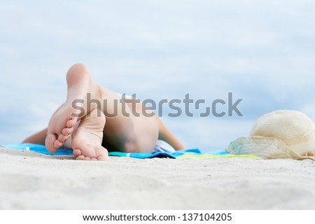 Image of feet soles of woman lying on sandy beach while sunbathing