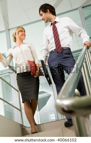 Image of female and male standing on marble ladder and looking at each other - stock photo