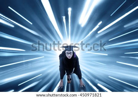 Image of female college student ready to run while wearing a mortarboard with fast motion blur background