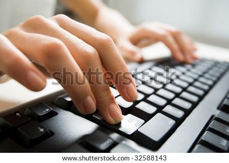Image of female fingers pushing enter key during computer work - stock photo