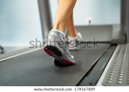 Image of female foot running on treadmill - stock photo