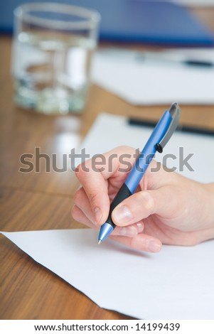 Image of female hand holding the pen over the paper