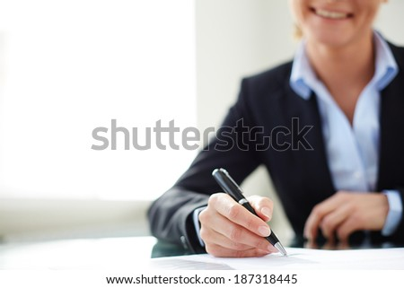 Image of female hand signing document at workplace - stock photo