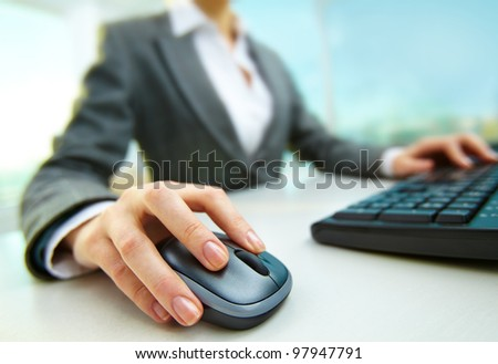 Image of female hands pushing keys of a computer mouse and keyboard