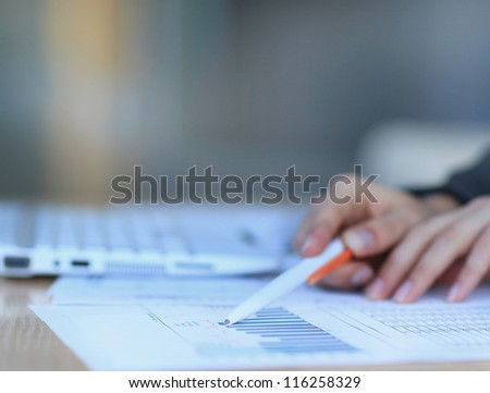 Image of female hands with pens over business document - stock photo
