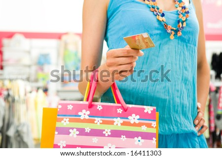 Image of female holding card in hand ready to pay for her shopping - stock photo