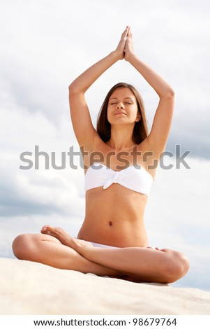 Image of female in white bikini meditating on sandy beach