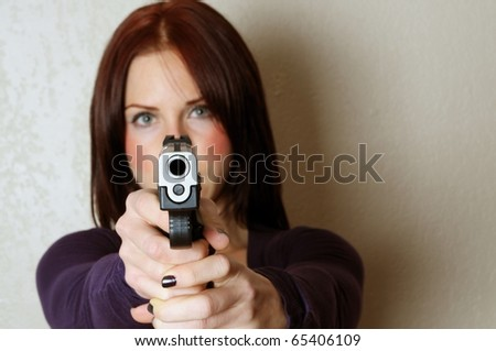 Image of female pointing a gun at somebody breaking and entering - stock photo