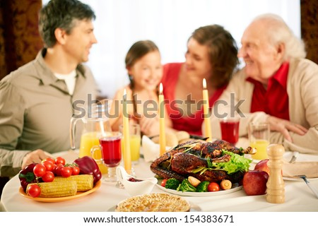 Image of festive table with family on background - stock photo