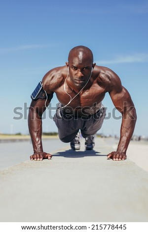 Image of fit young guy doing push-ups. Young fitness model exercising outdoors. - stock photo