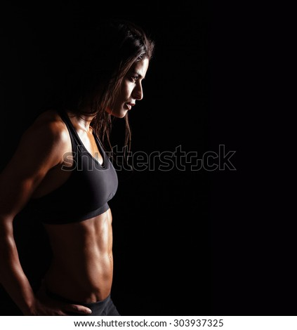 Image of fitness woman in sports clothing looking away on black background. Young female with perfect muscular body. Determination and confidence. - stock photo