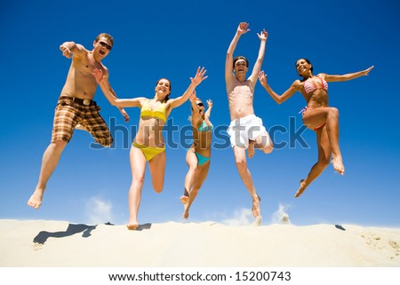 Image of five energetic people jumping at the beach - stock photo