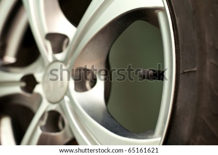 image of five pointed alloy wheels for the car and a valve, suitable for stylized arrangement of car