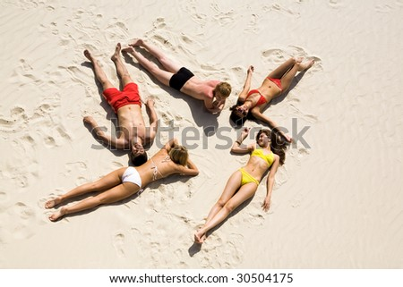 Image of five young people resting on the sand - stock photo