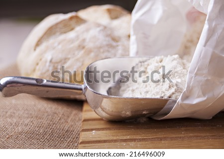 Image of flour, scoop and fresh loaf of bread.  - stock photo