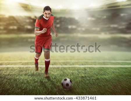 Image of football player dribbling ball on the field