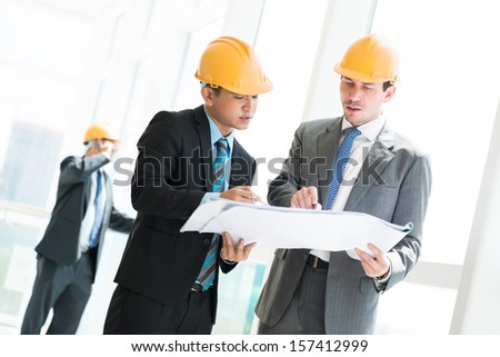 Image of foremen seriously discussing the constructor project on the foreground - stock photo