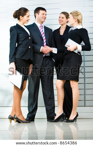 Image of four business people standing with handshaking of the business lady and her business partner at the front - stock photo