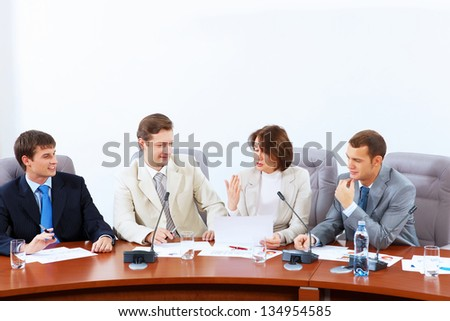 Image of four businesspeople discussing at meeting - stock photo