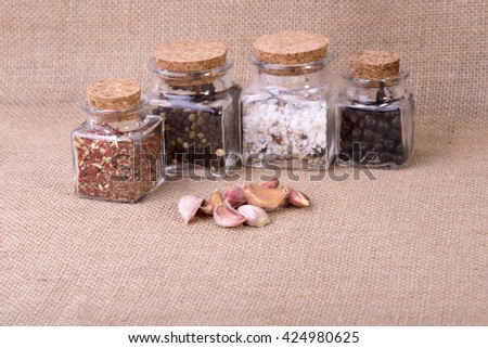 image of fresh garlic surrounded by containers with herbs - stock photo