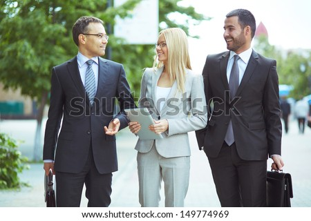 Image of friendly business team communicating outside