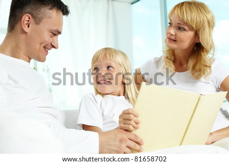 Image of friendly family interacting while reading book at home