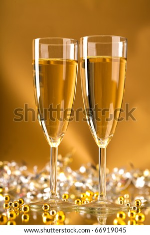Image of full champagne flutes with luxurious beads over golden background - stock photo