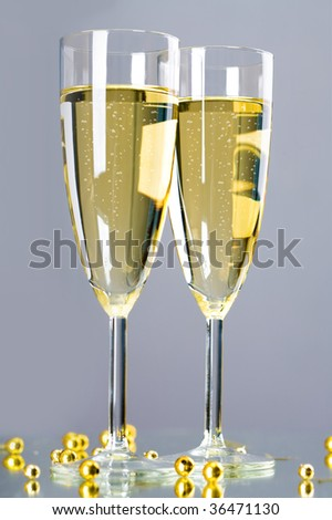 Image of full champagne flutes with several golden beads over grey background - stock photo