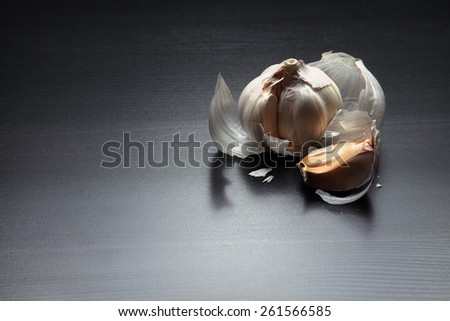 Image of garlic on black wooden table - stock photo