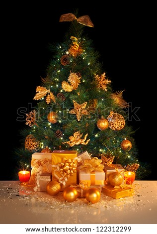 Image of gifts under beautiful Christmas tree isolated on black background, green fir tree decorated with golden balls, stars, angels and garland, different wrapped New Year presents, xmas surprise - stock photo