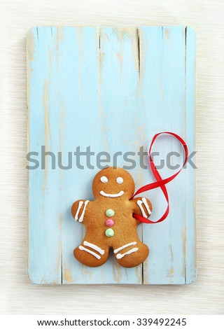 Image of Gingerbread man on blue vintage cutting board with copyspace - stock photo