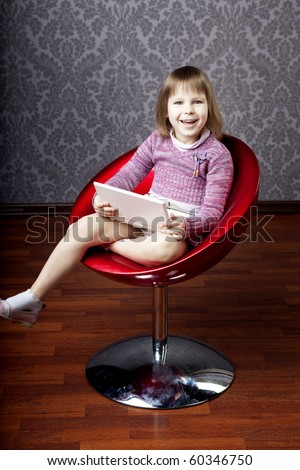 Image of girl sitting in a chair with a laptop - stock photo