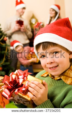 Image of glad boy with Christmas present on background of his brother and parents - stock photo
