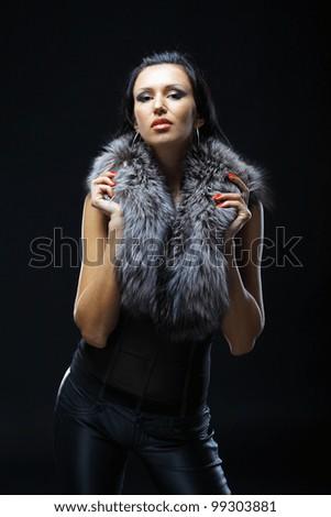 Image of glamorous woman wearing a fur. Dark background - stock photo