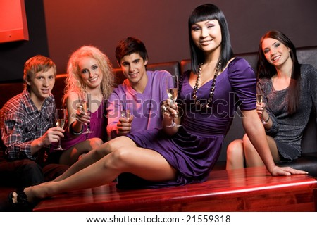 Image of glamorous woman with champagne sitting on table on background of her friends