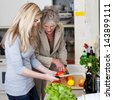 Image of grandmother and her granddaughter cutting fruits in the kitchen. - stock photo