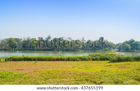 image of grass field and river on day time for background.